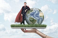 Businessman in mask and cape standing and resting one elbow on Earth globe, on top of digital tablet screen covered with. Grass, held by woman`s hand. Digital royalty free stock photos