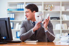 The businessman with mask in office hypocrisy concept. Businessman with mask in office hypocrisy concept Royalty Free Stock Images