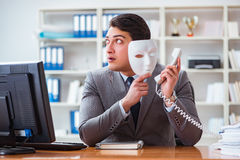 The businessman with mask in office hypocrisy concept. Businessman with mask in office hypocrisy concept Stock Photography