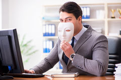 The businessman with mask in office hypocrisy concept. Businessman with mask in office hypocrisy concept Stock Photo
