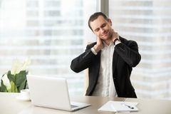 Businessman massaging his tense neck muscles. Businessman feeling pain in neck after sitting at desk. Tired man suffering of office syndrome after long hours stock photo