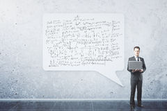 Businessman with mathematical formulas. Businessman with laptop standing near large abstract speech bubble with mathematical formulas Royalty Free Stock Images