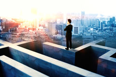Businessman on maze wall. Businessman on top of concrete maze wall looking into the distance on city background with sunlight Stock Photography