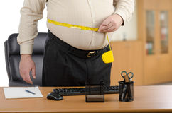 Businessman measures his waist by tape meter at the desk Stock Image