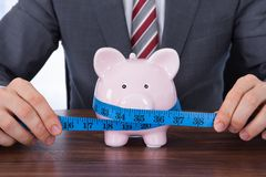 Businessman measuring piggybank with measure tape Royalty Free Stock Photo