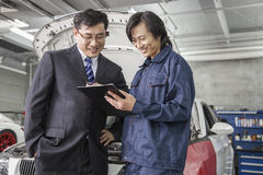 Businessman with Mechanic in Auto Repair Shop Stock Photo