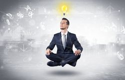 Businessman meditates with enlightenment concept. Businessman meditates with enlightenment data reports and financial conceptn royalty free stock photos