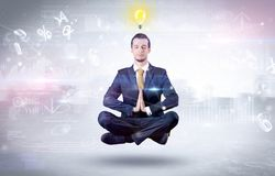 Businessman meditates with enlightenment concept. Businessman meditates with enlightenment data reports and financial concept royalty free stock photography