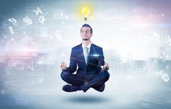 Businessman meditates with enlightenment concept. Businessman meditates with enlightenment data reports and financial conceptn royalty free stock photography