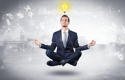 Businessman meditates with enlightenment concept. Businessman meditates with enlightenment data reports and financial conceptn stock images