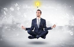 Businessman meditates with enlightenment concept. Businessman meditates with enlightenment data reports and financial concept stock image