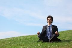 Businessman meditates sitting on meadow Royalty Free Stock Photography