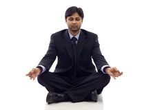 Businessman Meditating. Asian businessman sitting in lotus position isolated over white background Royalty Free Stock Photography