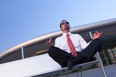 Businessman meditating. Calm balanced business person sitting in Yoga pose on bench meditating with office building in background Stock Images
