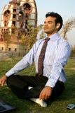 Businessman meditating. Young business man meditating near a temple Stock Photos