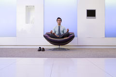Businessman meditating in armchair in foyer, portrait Stock Photo