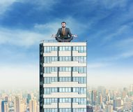 Businessman is meditating on the building royalty free stock photography