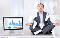 Businessman meditating by computer in office Stock Images