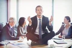 Businessman meditating in conference room Stock Image