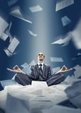 Businessman is meditating with documents. Businessman is meditating with flying around documents Royalty Free Stock Photos
