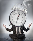 Businessman meditating with face covered by alarm clock Royalty Free Stock Images