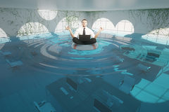 Businessman meditating in flooded office. Businessman with laptop meditating on lifebuoy in abstract flooded office interior. 3D Rendering Stock Images