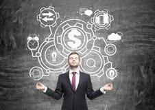 Businessman meditating in front of blackboard sketch Stock Photo