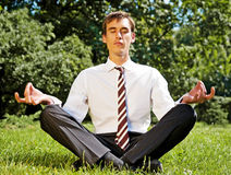 Businessman meditating on the grassland Royalty Free Stock Images