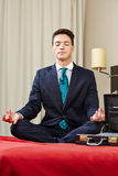 Businessman meditating in hotel room Royalty Free Stock Photography
