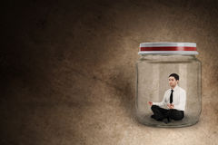 Businessman meditating in jar Royalty Free Stock Photos