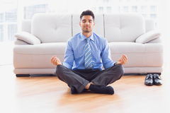 Businessman meditating in lotus pose on the floor Stock Images