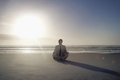 Businessman Meditating In Lotus Position On Beach. Full length of young businessman meditating in lotus position on beach Stock Images