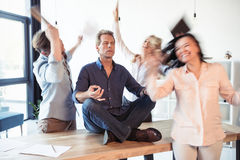 Businessman meditating in lotus position while coworkers celebrating success. Relaxed businessman meditating in lotus position while coworkers celebrating Royalty Free Stock Photography