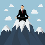 Businessman meditating on a Mountain peak Stock Photography