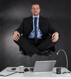 Businessman meditating in the office Stock Photography