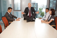 Businessman meditating on office desk Stock Image
