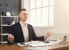 Young serious businessman relaxing in modern office. Businessman meditating at office. Male manager calming down and relaxing at his work table full of papers Stock Photography