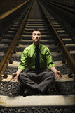 Businessman Meditating on Railroad Tracks. Stock Photo