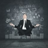 Businessman meditating with scribbles background Royalty Free Stock Photo
