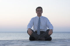 Businessman meditating by the sea Stock Photography