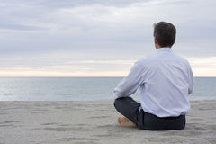 Businessman meditating at the sea. Businessman meditating on a beach at the sea Stock Images