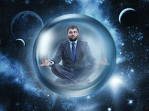 Businessman meditating in space Stock Photo