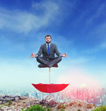 Businessman meditating. On the top of the umbrella against doentown Stock Photo