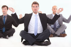Businessman meditating on white. Businessmen meditating on white in lotus position Royalty Free Stock Photos