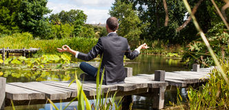 Businessman meditating on wooden path above water Stock Photography