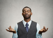 Businessman meditating. Young businessman meditating, eyes closed, grey wall background. Stress relief techniques at work concept. Take a deep breath Stock Images