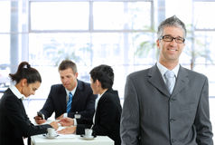 Businessman on meeting. Smiling businessman standing in front, businesspeople talking at desk in the background Royalty Free Stock Image