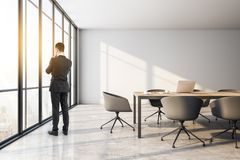 Businessman in meeting room. Thoughtful young businessman standing in modern meeting room interior with city view, daylight and furniture royalty free illustration