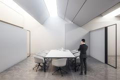 Businessman in meeting room. Thoughtful young businessman standing in modern white meeting room interior with furniture stock illustration