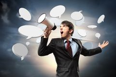 Businessman with megaphone. Young businessman in black suit screaming into megaphone Stock Photo